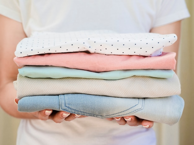 Close-up woman holding folded clean clothes