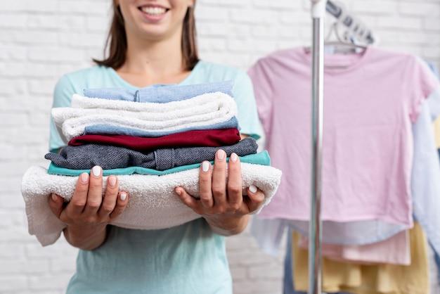 Крупным планом женщина, держащая сложенную одежду и полотенца