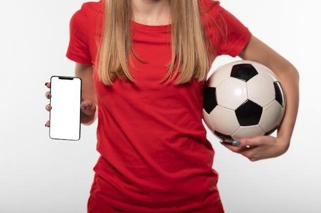 Крупным планом женщина, держащая футбольный мяч и телефон