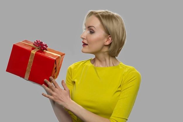 灰色の背景にギフトボックスを保持している女性を閉じます。包まれたプレゼントボックスを保持している幸せな満足の女性。特別な日のための贈り物。