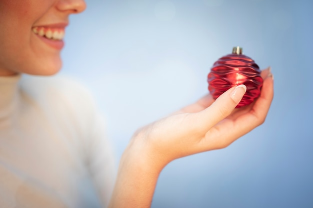 Close-up woman holding globe for fir tree