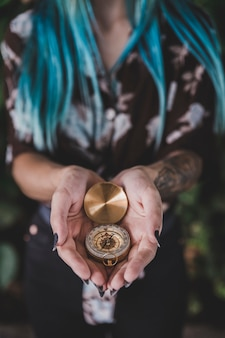 Close-up of woman holding golden vintage compass in hand
