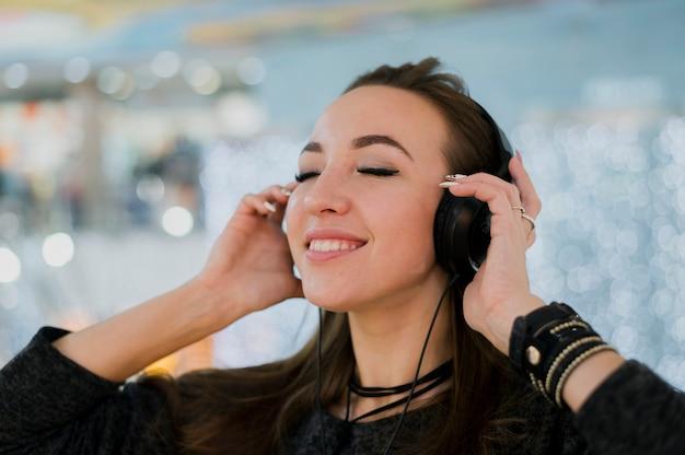 ショッピングモールで頭の上にヘッドフォンを保持しているクローズアップの女性