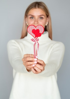 Close up woman holding heart decoration