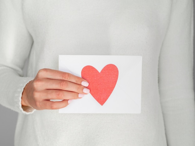 Close up woman holding heart envelope