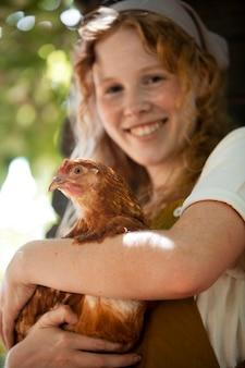 鶏を保持している女性をクローズアップ
