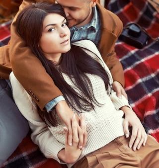 Primo piano della donna che tiene la mano del suo ragazzo e che si siede su una coperta