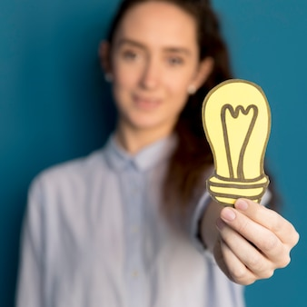 アイデアライトを保持しているクローズアップの女性