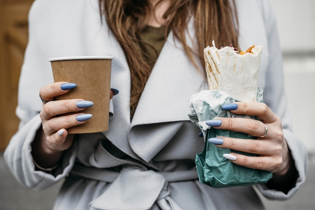 Close-up woman holding kebab and coffee