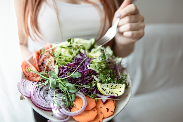 Close-up of a woman holding a large plate of freshly prepared vegetable salad at home.