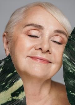 葉を保持しているクローズアップの女性