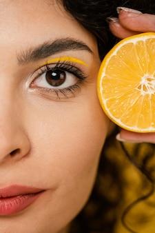 Donna del primo piano che tiene fetta di limone