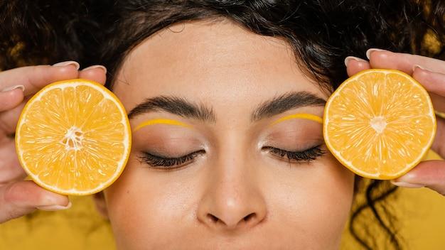 Крупным планом женщина, держащая дольки лимона