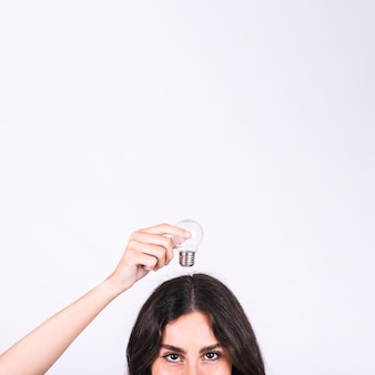 Primo piano di una donna che tiene la lampadina sopra la sua testa