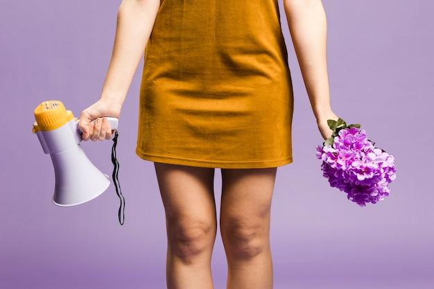 Крупным планом женщина держит мегафон и цветы