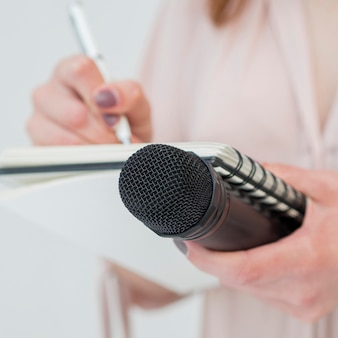 Close-up woman holding microphone and writing notes