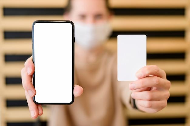 携帯電話とカードを保持しているクローズアップの女性