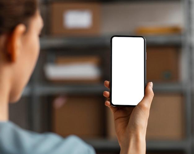Chiuda sulla donna che tiene mobile con schermo vuoto