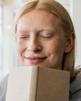 ノートブックを保持しているクローズアップの女性