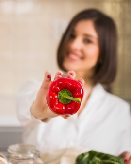 Donna del primo piano che tiene peperone dolce organico