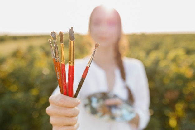 Close-up woman holding paintbrushes