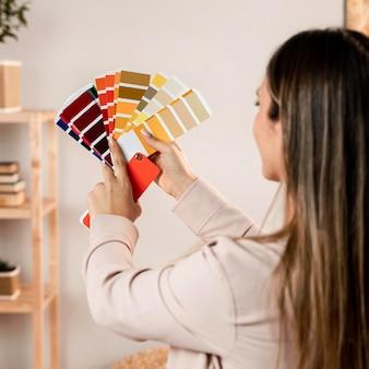 Крупным планом женщина, держащая палитру цветов