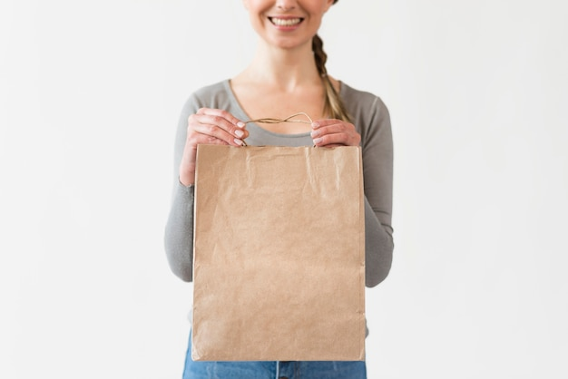 Close-up woman holding paper bag with groceries