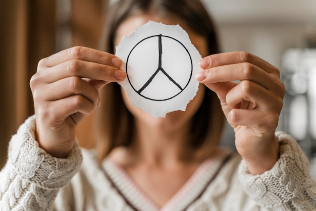 Close up of a woman holding a peace sign