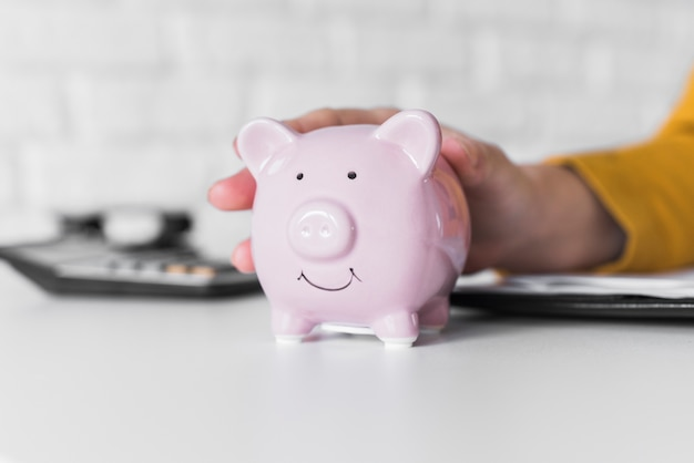 Close-up woman holding piggy bank