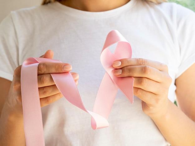 Close-up woman holding pink awareness ribbon