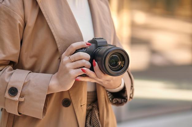 プロの写真カメラ、ベージュを保持しているクローズアップ女性