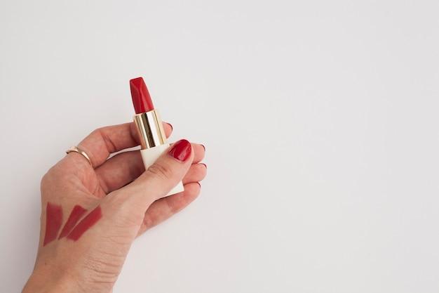 赤い口紅を保持しているクローズアップの女性
