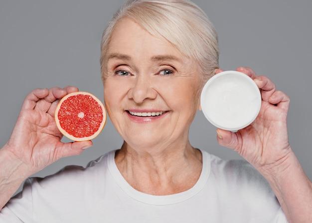 Donna del primo piano che tiene arancia rossa e crema