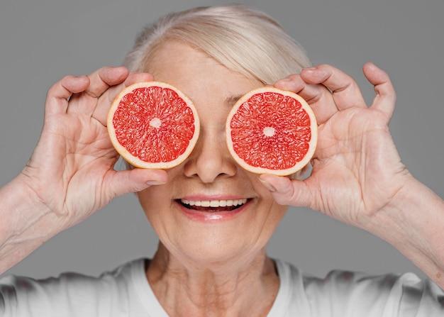 Donna del primo piano che tiene le fette dell'arancia rossa
