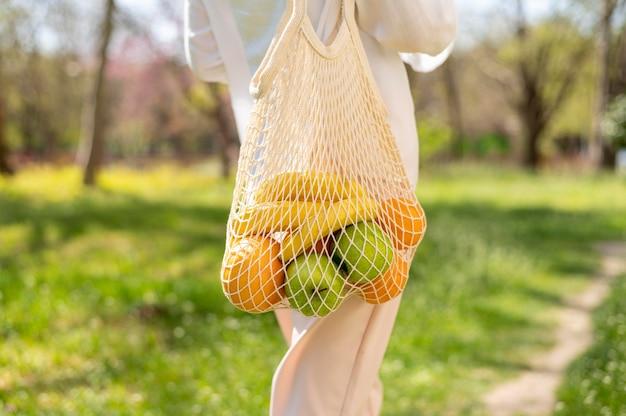 Close-up woman holding reusable bag walking outside