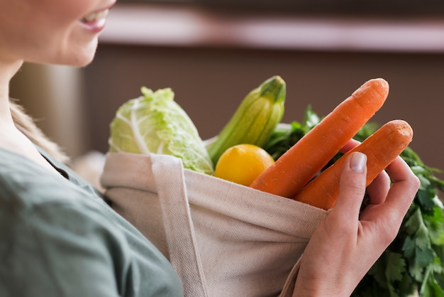 Close-up woman holding reusable bag with organic vegetables