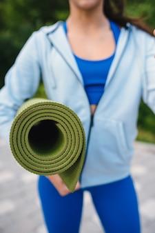 公園で運動した後、ロールフィットネスまたはヨガマットを保持しているクローズアップの女性。