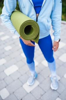 Close-up woman holding roll fitness or yoga mat after working out in the park.