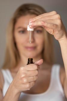 Close-up woman holding serum Premium Photo
