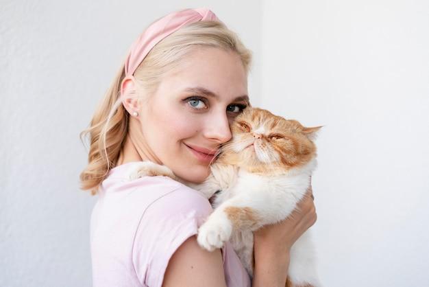 Крупным планом женщина, держащая сонную кошку