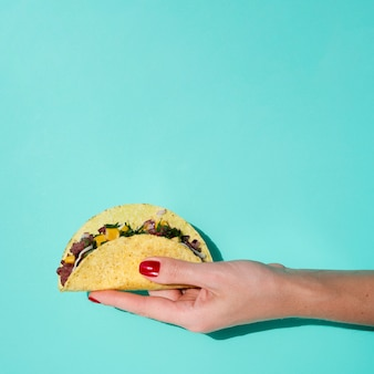 Close-up woman holding taco with green background and copy-space