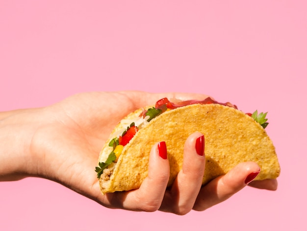 Close-up woman holding taco with pink background