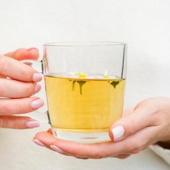 ガラスでお茶を保持しているクローズアップの女性