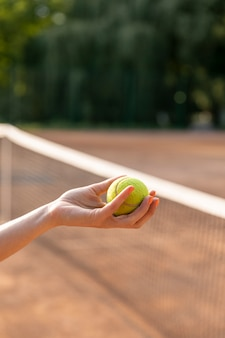 Close-up woman holding tennis ball