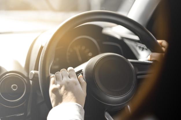 자동차 운전대를 잡고 있는 클로즈업 여성, 시골로 여행을 가기 위해 차를 운전하고 있으며, 차를 조종하기 위해 운전대를 잡고 있으며 안전하게 운전하려고 합니다.