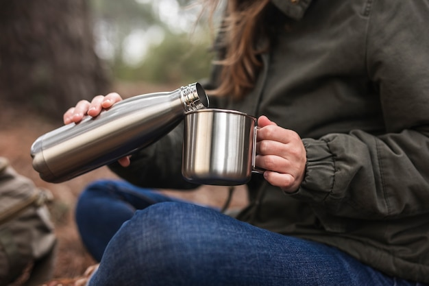 Close-up woman holding thermos and mug