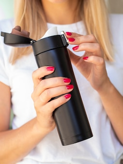 Close-up woman holding a thermos