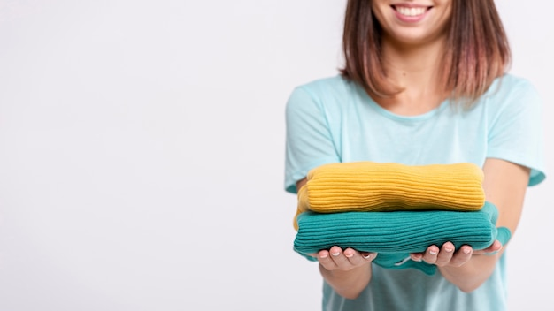 Close-up woman holding up colourful sweaters