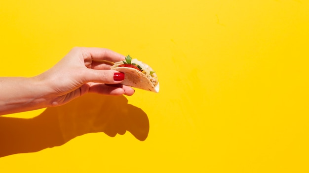 Close-up woman holding up delicious taco