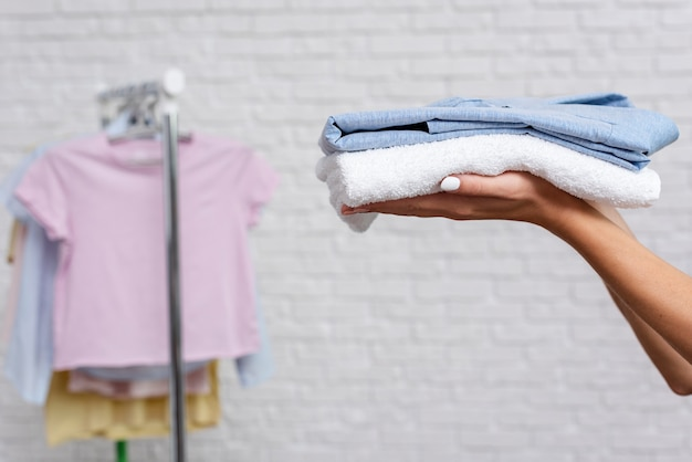 Close-up woman holding up folded shirt and towel